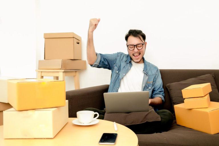 Man rejoicing while looking at his laptop and and being surrounded with boxes