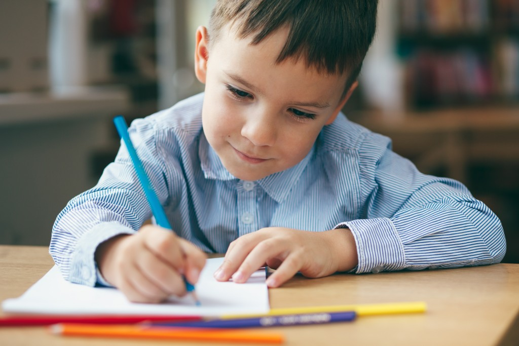 child writing on notebook