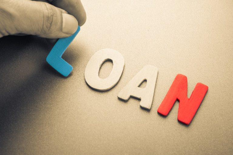 Hand arrange wood letters as Loan word