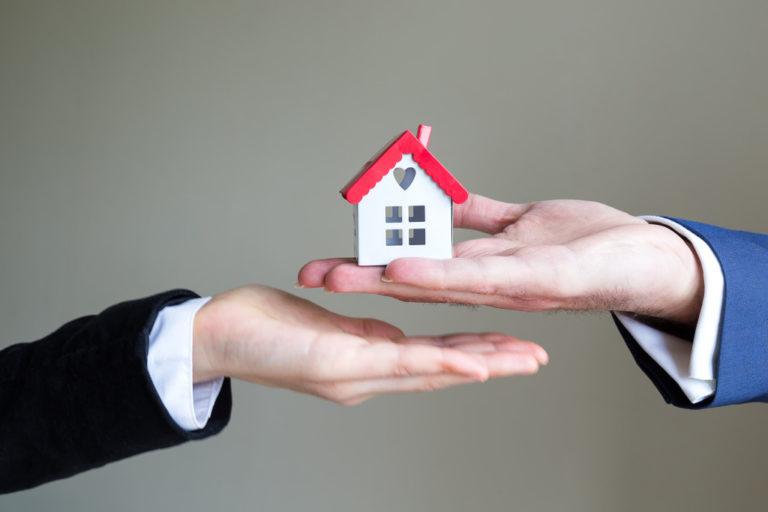 handing over a miniature house
