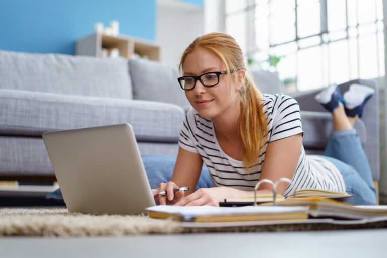 woman laying down on the floor working on laptop