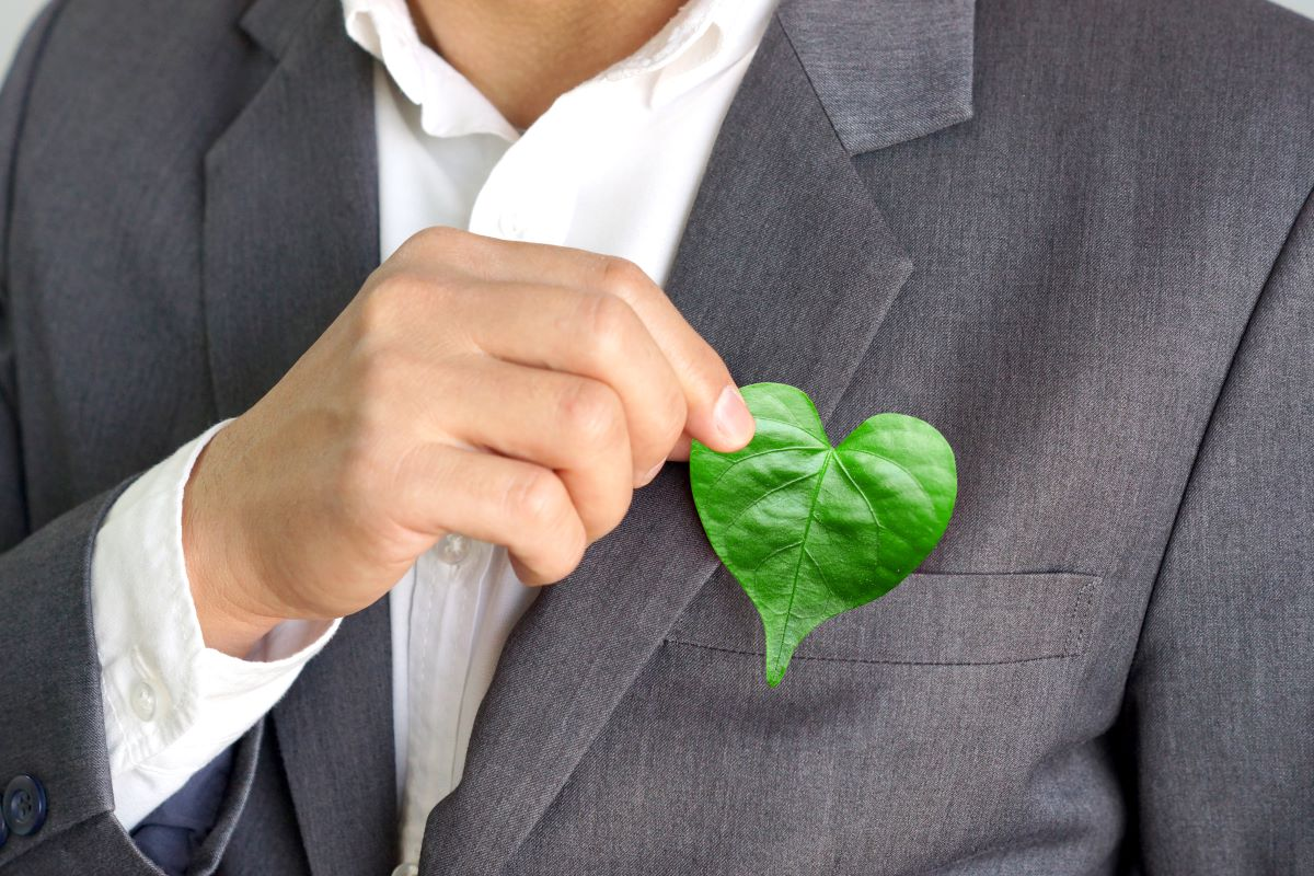business man holding heart shaped leaf